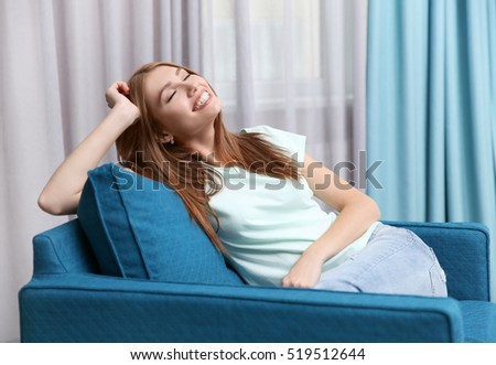 Beautiful girl relaxing on armchair