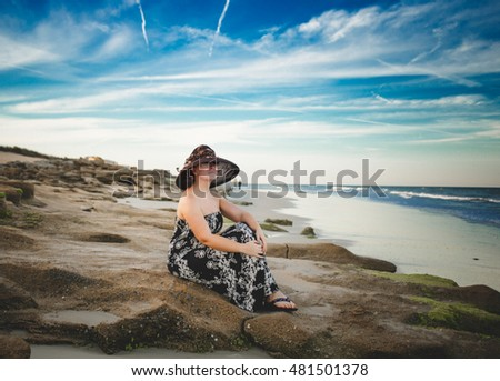 Beautiful girl relaxing on the beach looking at the horizon