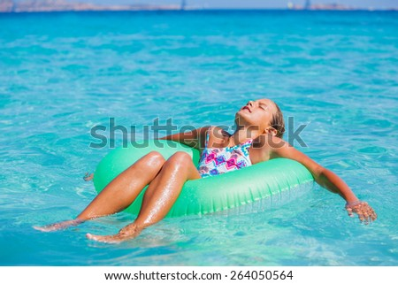 Beautiful girl relaxing on the inflatable rubber circle in the sea