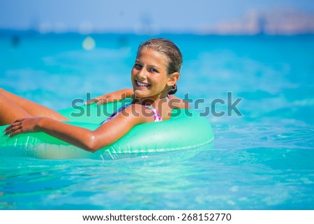 Beautiful girl relaxing on the inflatable rubber circle in the sea - stock photo