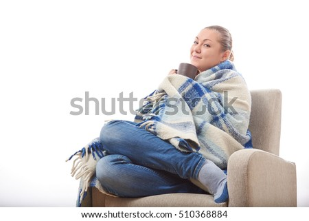 Beautiful girl resting and drinking tea sitting wrapped in a woolen plaid blanket.