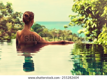 Beautiful girl rests in the swimming pool , sunbathing. Spa treatments. - stock photo