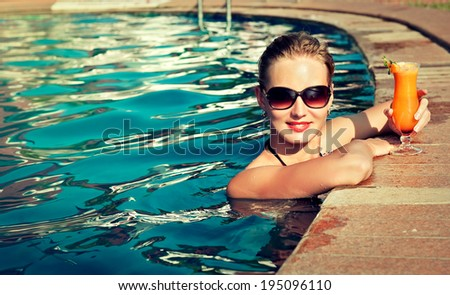 Beautiful girl rests near the swimming pool , sunbathing. Spa treatments. - stock photo
