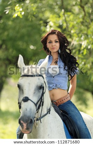 Beautiful girl rides a horse in nature