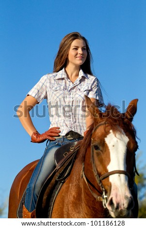 Beautiful girl  riding a horse against blue sky