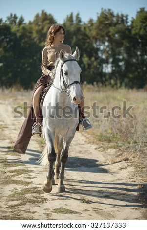 Beautiful girl riding a white horse in a field in profile to the camera.