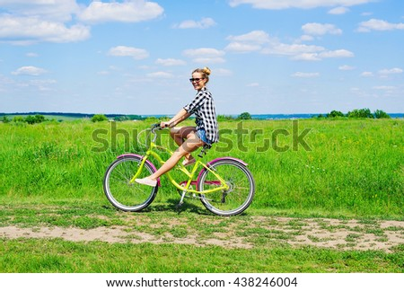 Beautiful girl riding bicycle outdoors across the green sunny field - stock photo