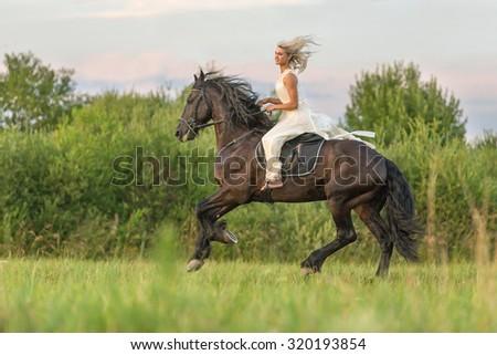 Beautiful girl riding black stallion. - stock photo