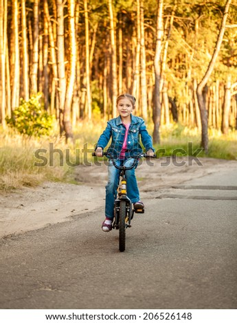 Beautiful girl riding her bike on road at forest - stock photo
