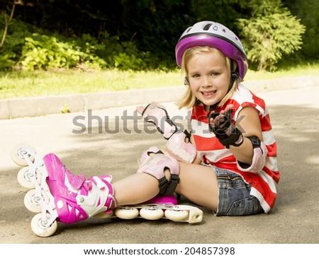 beautiful girl roller skating and fell upset - stock photo