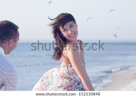 Beautiful Girl running from her boyfriend during summer time fun on the seashore - stock photo
