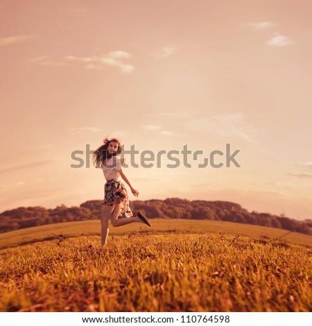 beautiful girl running on summer field - stock photo