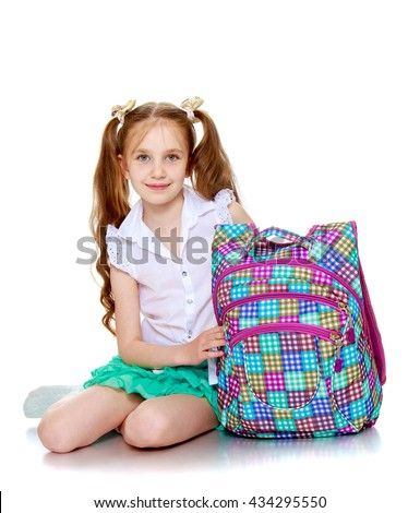 Beautiful girl schoolgirl with long pigtails on her head , sitting on the floor along with his school satchel-Isolated on white background - stock photo