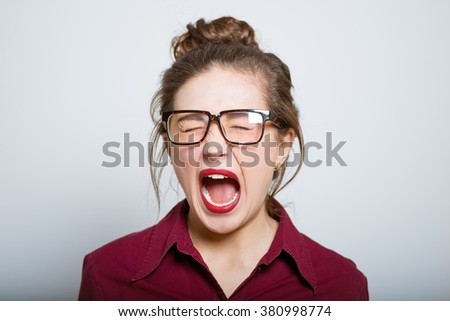 Beautiful girl screaming angry, isolated on gray background - stock photo