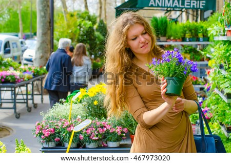 Beautiful girl selecting flowers in a Parisian outdoor flower shop