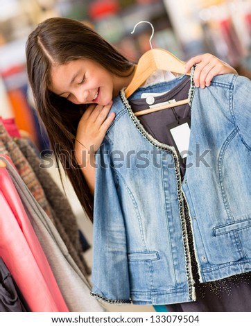 Beautiful girl shopping for clothes at a retail store