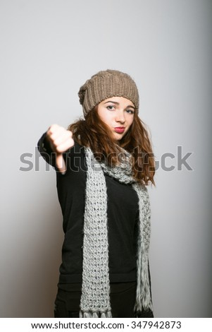 beautiful girl showing thumbs down in winter clothes, Christmas and New Year concept shot isolated on gray background