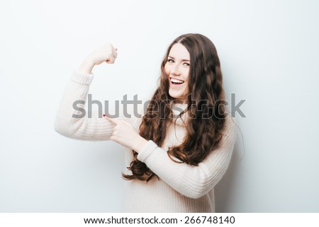 beautiful girl shows what she's strong, boy outfit - stock photo