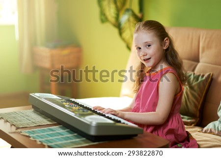 beautiful girl sings while playing on an electronic piano - stock photo