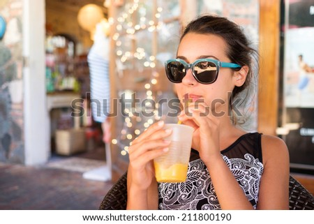 Beautiful girl sipping a smoothie outdoors in a restaurant setting. - stock photo