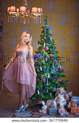 beautiful girl sits near decorated Christmas tree - stock photo