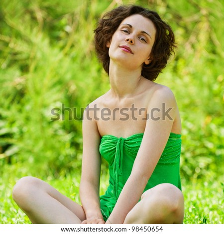 Beautiful girl sits on lawn. - stock photo