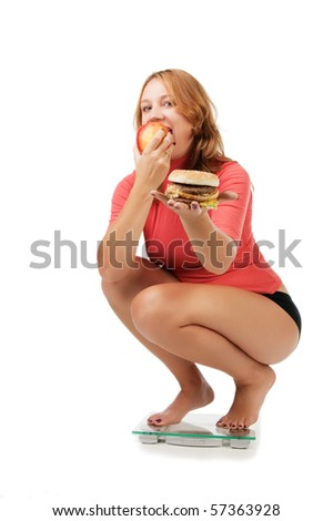 beautiful girl sits on scales and chooses  apple instead sandwich, isolated on white - stock photo