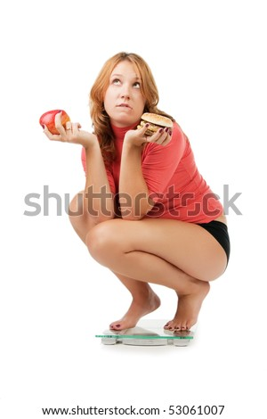 beautiful girl sits on scales and chooses between an apple and a sandwich, isolated on white - stock photo