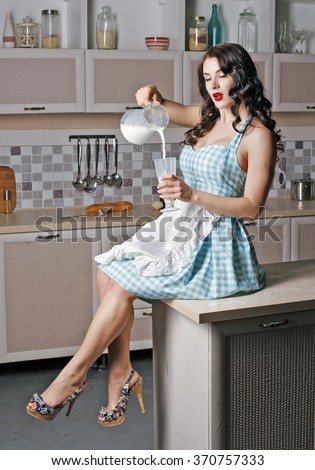 beautiful girl sits on the table and pours milk from a carafe into a glass,in the kitchen