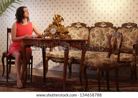 beautiful girl sitting at an old desk - stock photo