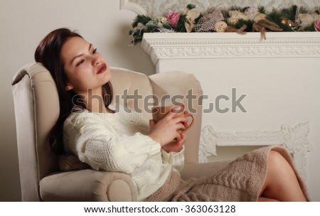 Beautiful girl sitting in a chair near the fireplace and drink hot tea