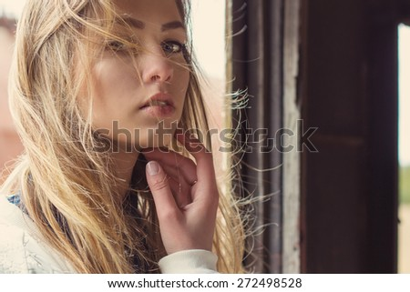 beautiful girl sitting in an abandoned train and a strong wind develops her hair - stock photo