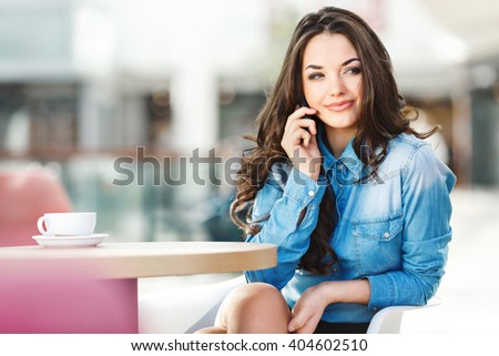 Beautiful girl sitting in cafe in shopping mall, looking aside, smiling and holding phone with one hand near ear. Coffee on table. Wearing blue jeans blouse, nice make up. Indoor, waist up, closeup