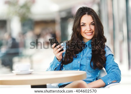 Beautiful girl sitting in cafe in shopping mall, looking at camera and holding phone. Coffee on table. Wearing blue jeans blouse, nice make up. Indoor, waist up, closeup