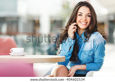 Beautiful girl sitting in cafe in shopping mall, looking at camera, smiling and holding phone with one hand near ear. Coffee on table. Wearing blue jeans blouse, nice make up. Indoor, waist up