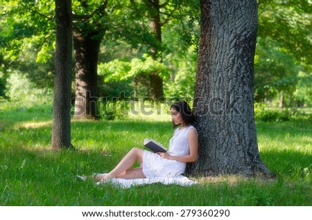 Beautiful girl sitting in forest and reading book on sunny summer day. - stock photo