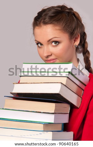 beautiful girl sitting in front of books,gray background - stock photo