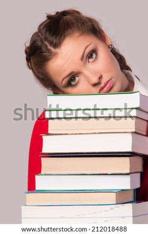 beautiful girl sitting in front of books, grey background - stock photo
