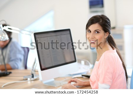 Beautiful girl sitting in office in front of desktop - stock photo