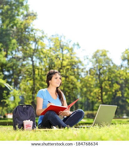 Beautiful girl sitting in park and writing in notebook shot with tilt and shift lens - stock photo
