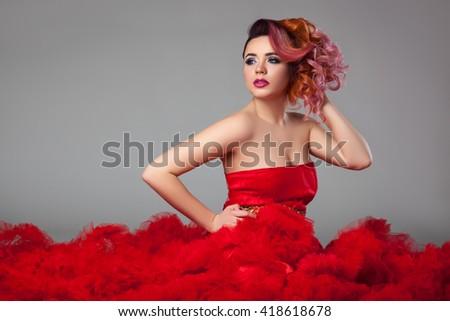 Beautiful girl sitting in red dress. - stock photo