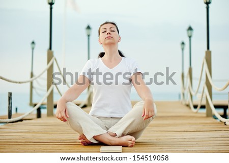 beautiful girl sitting in the lotus position on a pier with his eyes closed - stock photo
