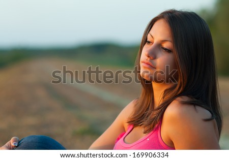 Beautiful girl sitting in the nature on sunny spring day. - stock photo