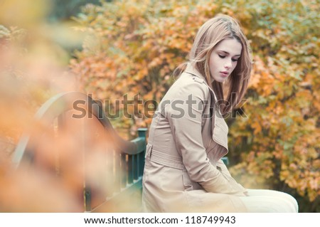 beautiful girl sitting in the park waiting for