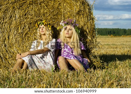 beautiful girl sitting near the haystacks