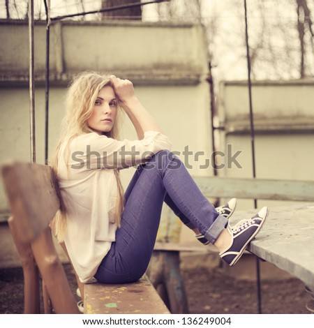 beautiful girl sitting on a bench - stock photo
