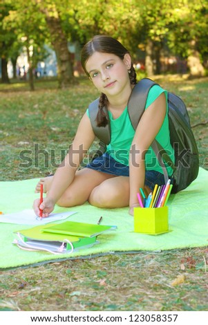 beautiful girl sitting on a blanket in the park and learn, soft focus, best focus on the face girls