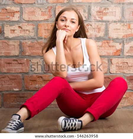 beautiful girl sitting on a brick wall background, studio portrait - stock photo