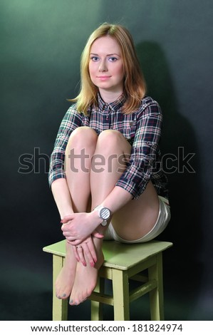 Beautiful girl sitting on a chair - stock photo