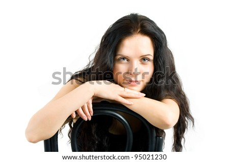 beautiful girl sitting on a chair and looks into the camera - stock photo